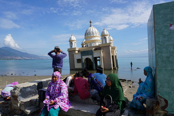 Muslims gather as they attend mass prayers to mark one year after Central Sulawesi earthquake and tsunami, near a damaged mosque in Palu