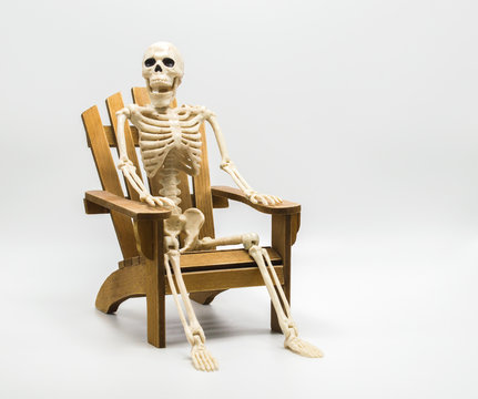 a whimsical Halloween skeleton sitting in a wooden Adirondack chair isolated on white