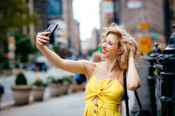 Portrait of a young woman taking a selfie on the street in New York City