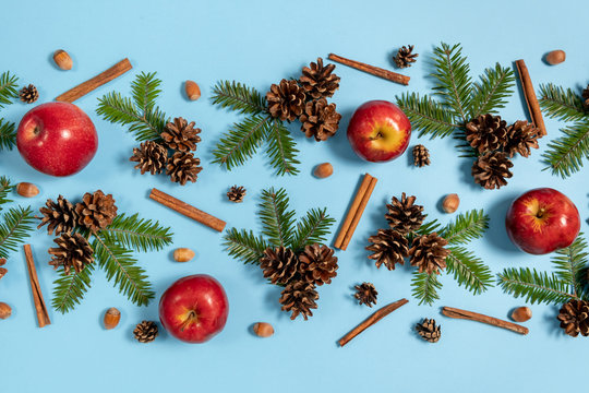 Christmas or winter composition. Frame made of fir tree branches, pine, acorn, red apple and cinnamon on pastel blue background. Christmas, winter, new year concept. Flat lay, top view, copy space