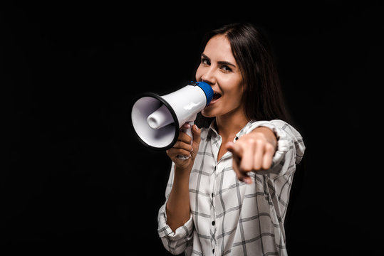 selective focus of happy woman holding megaphone and pointing with finger isolated on black