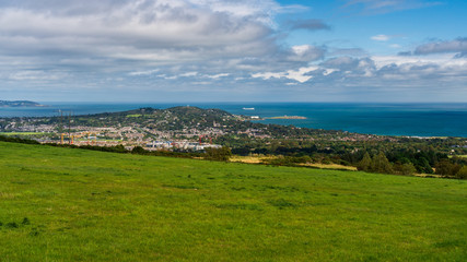 Scenic green landscape in Dublin Mountains with an amazing view over the city and the Irish Sea. Countryside blue cloudy skies over a beautiful grass meadow.