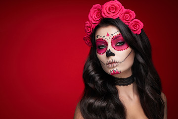 Portrait of a woman with sugar skull makeup over red background. Halloween costume and make-up....