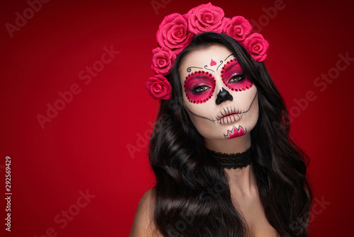 Portrait of a woman with sugar skull makeup over red background. Halloween costume and make-up. Portrait of Calavera Catrina
