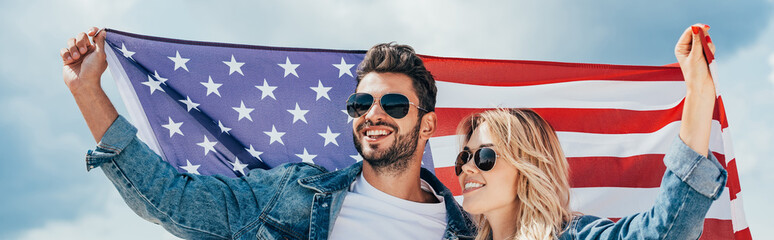 Fotomurales - panoramic shot of attractive woman and handsome man smiling and holding american flag