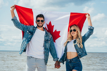 Fotomurales - blonde woman and man in jacket holding canadian flag