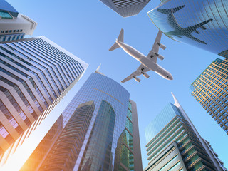 Tuinposter Aan het plafond Airplane flying over skyscrapers n city downtown district. Business corporate travel background concept.