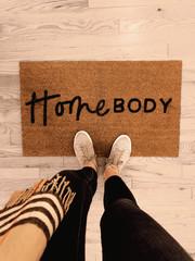 Door mat with Homebody written on it with shoes floor
