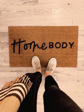 Door mat with Homebody written on it with shoes floor