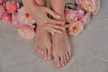 Foto op Canvas Manicure Ideal done manicure and pedicure. Women's legs and hands. On a marble background.