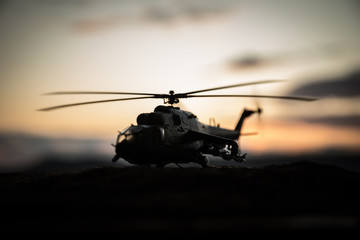 Photo sur Plexiglas Hélicoptère Silhouette of military helicopter ready to fly from conflict zone. Decorated night footage with helicopter starting in desert with foggy toned backlit. Selective focus.