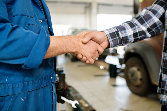 Handshake of technician of car repair service in workwear and one of clients