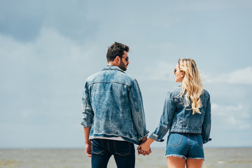 Fotomurales - back view of woman and man in denim jackets looking at each other and holding hands