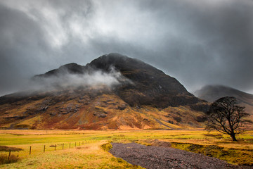 A moody view of a rocky hill in Glencoe, with red, orange and green. Scotland.