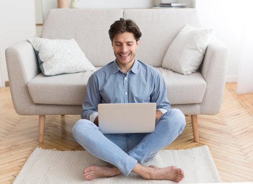 Successful Freelancer Working On Laptop Sitting On Floor At Home
