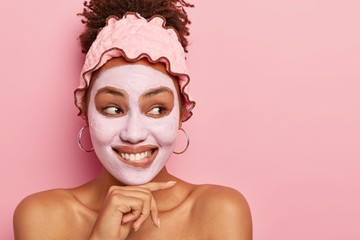 Portrait of beautiful young African American woman touches chin, has gentle toothy smile, applies clay mask for rejuvenation, stands bare shoulders against pink background. Beauty and spa concept
