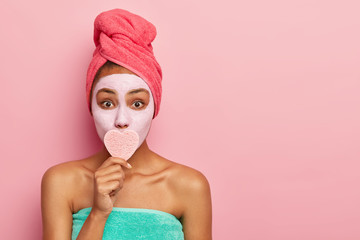 Horizontal shot of surprised lady covers mouth with heart shaped sponge, removes makeup, applies clay mask on face for looking young, wears wrapped towel on head, poses over pink wall, copy space