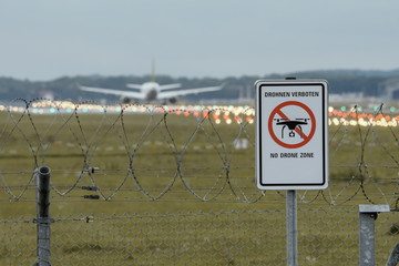 """Prohibition sign at German airport """"Dronen Verboten"""" with aircraft ab runway in the background"""