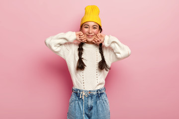 Pretty mixed race female dressed in fashionable yellow hat, white sweater and jeans, has enthusiastic and charming look in camera, glad expression, isolated over pink background, has two combed plaits