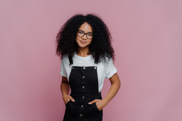 Portrait of happy curly African American woman keeps hands in pockets of sarafan, wears transparent glasses, meets with friends during weekend, models over violet background, has delighted look