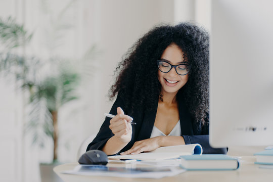 Photo of pleased curly haired woman writes down some information, holds pen, has smile, wears optical glasses and formal clothes poses at workplace with computer. Student writes ideas for course paper