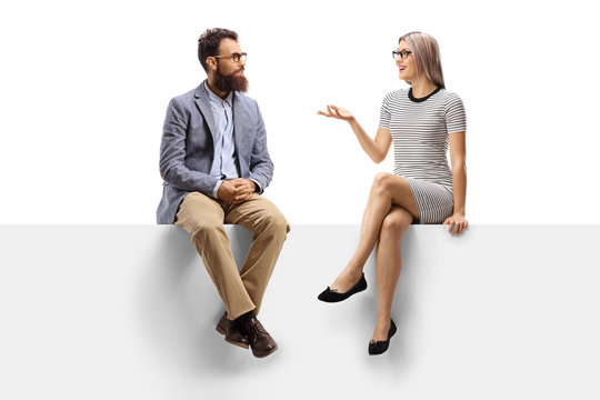 Young woman having a conversation with a bearded man while sitting on a panel