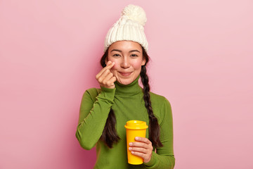 Photo of attractive young Asian girl makes korean like sign, shapes little heart near cheek, expresses love to boyfriend, wears warm hat and casual jumper, drinks takeaway coffee, poses indoor