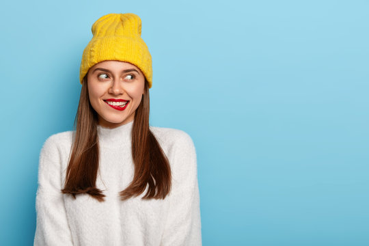 Attractive young woman bites red lips, thinks about something, looks away, has straight dark hair, wears yellow hat, warm white sweater, feels happiness, ready for walk outdoor during winter time