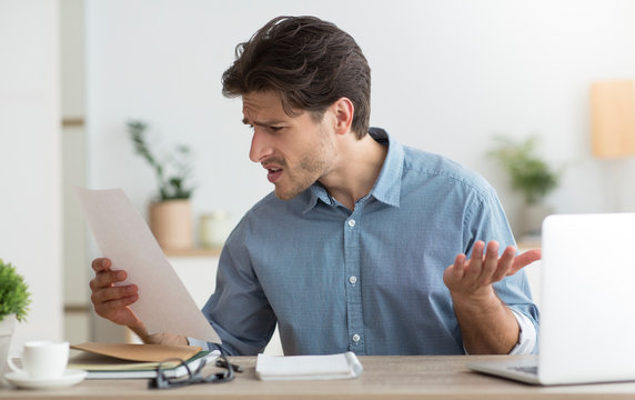 Discontented Guy Reading Tax Notification Sitting At Laptop In Office