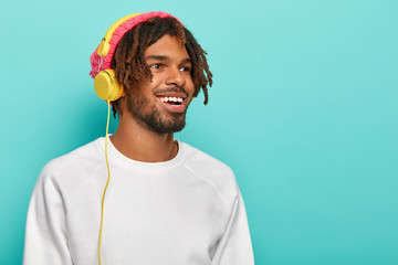 Optimistic unshaven male student has dreads, wears headphones on ears, has fun, listens favourite audio track, wears white clothes, looks aside, smiles pleasantly, things about something good