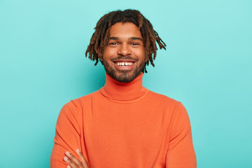 Positive emotions concept. Handsome dark skinned hipster with dreads has pleasant smile, has white teeth, happy to hear good news, wears bright clothes, isolated over blue background, has lucky day