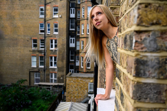 Portrait of young woman wistfully looking out of the window of an old brick building and hoping for better things to come in London, England