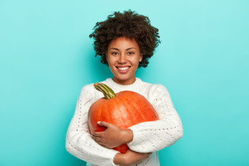 Autumn harvesting, food and Halloween holiday concept. Cheerful curly African American woman embraces ripe pumpkin, smiles pleasantly, dressed in white sweater. Girl with thanksgiving symbol.