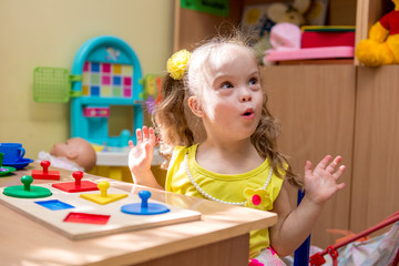 Girl with down syndrom developing motor skills in rehab center for special children