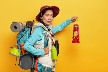 Horizontal shot of dissatisfied mixed race female backpacker wears stylish hat and warm vest, holds kerosene lamp to explore surroundings in darkness, uses necessary equipment for traveling.