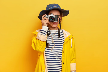 Female traveler makes memorable photos during trip, holds retro camera, takes images of beautiful landscape or place, dressed in striped jumper, raincoat and hat, isolated over yellow background