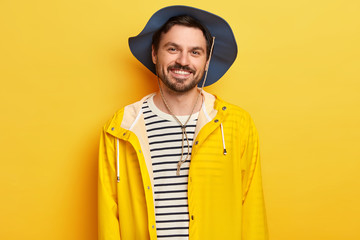 Horizontal shot of pleased Caucasian man wears hat, yellow raincoat, spends leisure time actively, poses indoor, expresses good emotions, has stubble, stands indoor. Happy male model travels alone