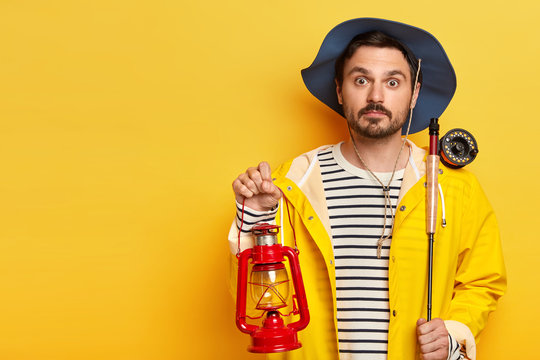Surprised fisherman holds fishing rod and kerosene lamp, has overnight fishing trip, wears hat and raincoat, poses over yellow background, copy space for your advertising area. Angling concept