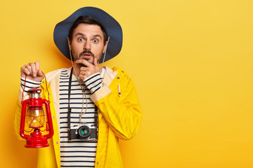 Horizontal view of pensive male traveler holds chin, looks straigtly at camera, holds gaslamp, dressed in casual clothes, uses camera for taking pics, stands against yellow background free space aside