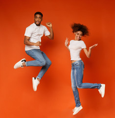 Carefree african american man and woman jumping in air