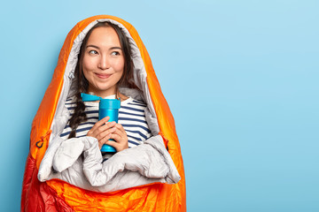 Delighted Asian female tourist holds flask with hot drink, wrapped in warm sleep bag, spends night...