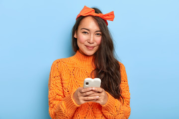 Portrait of happy pretty Asian woman with long hair, wears headband and orange sweater, holds mobile phone for chatting, downloads new application, updates software, looks positively at camera