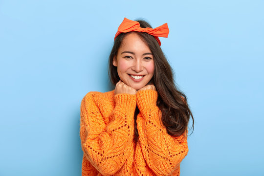 Portrait of glad brunette millennial female keeps both hands under chin, smiles pleasantly, wears orange bow headband, warm orange knitted sweater, expresses sincere feelings. Face expressions
