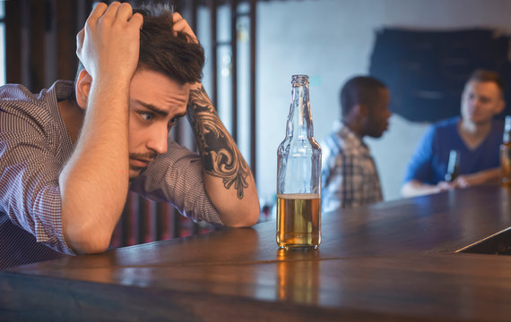 Troubled young man sitting alone at bar