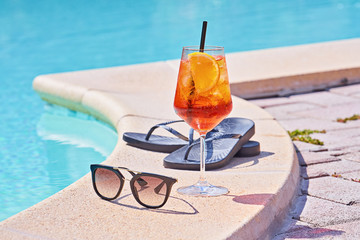 Wineglass of cold cocktail Aperol spritz near swimming pool