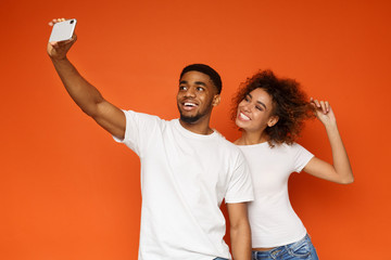 Positive african couple in love making selfie on smartphone
