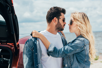 Fotomurales - attractive woman and handsome man in denim jackets kissing outside