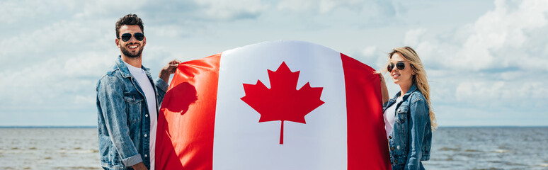 Fotomurales - panoramic shot of attractive woman and handsome man smiling and holding canadian flag