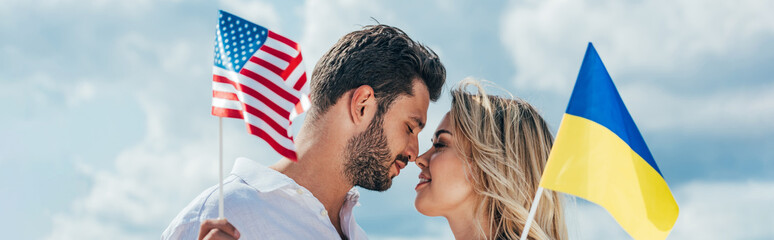 Fotomurales - panoramic shot of attractive woman and handsome man smiling and holding american and ukrainian flags