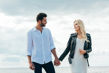Fotomurales - attractive woman and handsome man smiling and holding hands